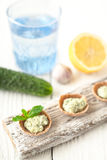 Crisp bread with tzatziki on the white wooden board vertical Royalty Free Stock Photos