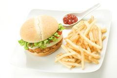 Crisp chicken burger tomato onion cheese lettuce Royalty Free Stock Image