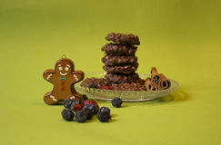 Crisp Chocolate Cookies and the gingerbread man. Rustic Holiday Feeling with chocolate cookies, cinnamon sticks, dry fruits and a tiny gingerbread man Royalty Free Stock Photography