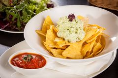 Crisp corn nachos with guacamole sauce Royalty Free Stock Photography