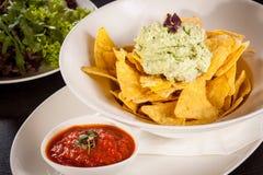 Crisp corn nachos with guacamole sauce Stock Image