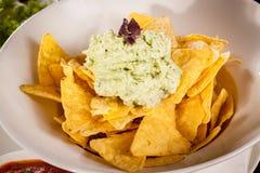 Crisp corn nachos with guacamole sauce Royalty Free Stock Images
