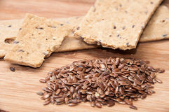 Crisp diet plates made of linen and linen seeds on the wooden bo. Ard Royalty Free Stock Images