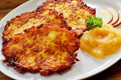 Crisp Fried Potato Rosti Served with Applesauce. Close Up Still Life of Crisp Fried Potato Rosti Patties Served on Modern White Plate with Pureed Applesauce and royalty free stock photos