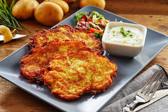 Crisp Fried Potato Rosti Served with Salad and Dip. Trio of Crisp Fried Potato Rosti Patties Served on Modern Rectangle Plate with Side Salad and Creamy Dressing stock photos
