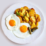 Crisp fried potato slices with two fried eggs Stock Image