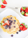 Crisp golden fresh baked waffle topped with strawberries on whit Royalty Free Stock Photos