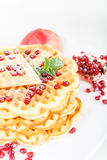 Crisp golden fresh baked waffle topped with strawberries on whit Royalty Free Stock Images