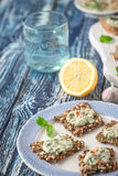Crisp grain bread with tzatziki on the  blue ceramic plate vertical. Crisp grain bread with tzatziki on the  blue ceramic plate on the blue wooden table vertical Royalty Free Stock Photography