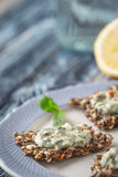Crisp grain bread with tzatziki on the  blue ceramic plate. On the blue wooden table vertical Stock Image