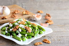Crisp green bean salad recipe. Delicious green beans salad with creamy cheese, crunchy walnuts, garlic and spices on a plate Royalty Free Stock Image