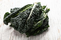 Crisp organic green lacinato kale. On white weathered wood background Royalty Free Stock Image