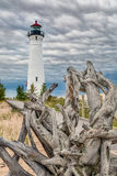 Crisp Point Driftwood. With a large piece of weathered driftwood in the foreground, Upper Peninsula Michigan's Crisp Point Lighthouse stands against a sky with Royalty Free Stock Photo