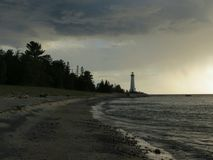 Crisp Point Lighthouse Before the Storm. A spring thunderstorm bares down on the beacon Crisp Point Lighthouse as it guards shipping on Lake Superior near the Royalty Free Stock Photography