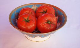 Crisp red beef tomatoes in a bon china porcelain bowl. A bon china porcelain bowl filled with beef tomatoes royalty free stock images