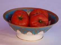 A bon china porcelain bowl filled with beef tomatoes. Crisp red beef tomatoes in a bon china porcelain bowl stock photo