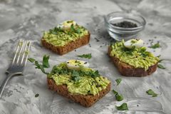 Crisp rye toasts with avocado and quail eggs. On table royalty free stock photos