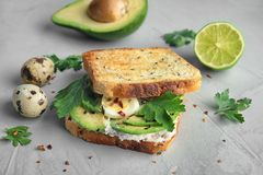 Crisp toast with sliced avocado, cream cheese. And quail eggs on table, closeup stock image