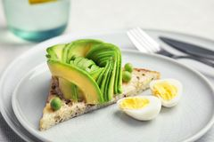 Crisp toast with sliced avocado and quail egg. On plate, closeup Royalty Free Stock Photo