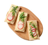 Crispbread with butter, radish and arugula. Crispbread with radish and arugula on cutting board Royalty Free Stock Images