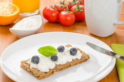 Crispbread with cream cheese and blueberries on a table Stock Photo
