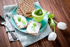 Crispbread with Cream Cheese and fresh herbs on a wooden Board royalty free stock photography