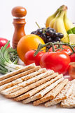 Crispbread with fresh fruits and vegetables. On white Royalty Free Stock Images
