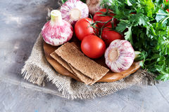 Crispbread and fresh vegetables Tomatoes garlic dill parsley Wooden board Copy space Vegetables for salad Copy space. Crispbread and fresh vegetables Tomatoes Stock Photos