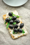 Crispbread with fromage, olives and herbs Royalty Free Stock Image