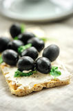 Crispbread with fromage, olives and herbs Royalty Free Stock Photo