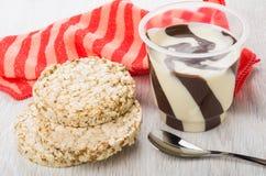 Crispbread, jar with dairy-chocolate paste, napkin, spoon on tab. Crispbread, opened jar with dairy-chocolate paste, red napkin, spoon on wooden table royalty free stock photo