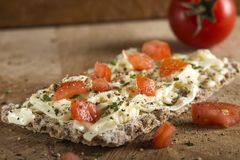 Crispbread with melted cheese and pieces of cherry tomatoes seas Royalty Free Stock Photo