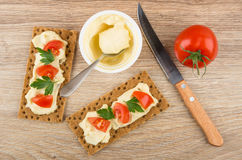 Crispbread with melted cheese, tomatoes, parsley, spoon and knif Stock Photos