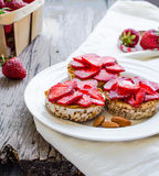 Crispbread with peanut butter and fresh strawberries on a  round Royalty Free Stock Images