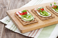 Crispbread with tomatoes, radish, cucumber and arugula Royalty Free Stock Photography