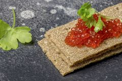 Crispbreads with caviar and parsley at black background stock photos
