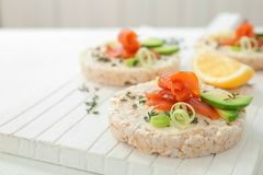Crispbreads with fresh sliced salmon fillet and avocado on wooden board, closeup stock photos