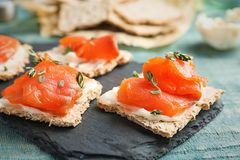 Crispbreads with fresh sliced salmon fillet. On slate board royalty free stock photography