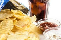 Crisps and coke. Glass of coke potato crisps and ketchup and mayonnaise stock photography
