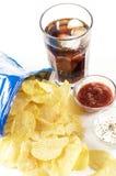 Crisps and coke. Glass of coke potato crisps and ketchup and mayonnaise royalty free stock image