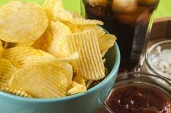 Crisps and coke. Glass of coke potato crisps and ketchup and mayonnaise on bamboo tray stock image