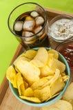 Crisps and coke. Glass of coke potato crisps and ketchup and mayonnaise on bamboo tray Stock Photography