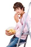 Crisps. Handsome teenage male eats crisps stock photo