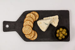 Crispy biscuits, cheese and bowl of green olives on chopping board Royalty Free Stock Photo