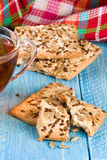 Crispy bread with seeds of sunflower, flax and sesame seeds with a cup of tea on a blue wooden background Stock Photography
