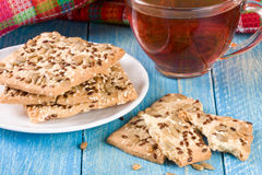 Crispy bread with seeds of sunflower, flax and sesame seeds with a cup of tea on a blue wooden background Royalty Free Stock Image