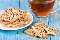 Crispy bread with seeds of sunflower, flax and sesame seeds with a cup of tea on a blue wooden background Stock Image