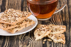 Crispy bread with seeds of sunflower, flax and sesame seeds with a cup of tea on a dark wooden background Stock Photo