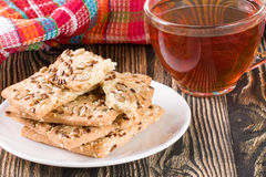 Crispy bread with seeds of sunflower, flax and sesame seeds with a cup of tea on a dark wooden background Stock Images