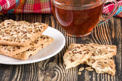 Crispy bread with seeds of sunflower, flax and sesame seeds with a cup of tea on a dark wooden background Royalty Free Stock Images